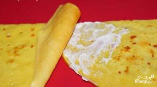 """4 блина разрежьте пополам, а затем сложите их в длинную цепочку. Блины должны лежать немного внахлест, место стыка смажьте плавленным сыром. Пятый блин будет использован для изготовления """"корешков""""."""