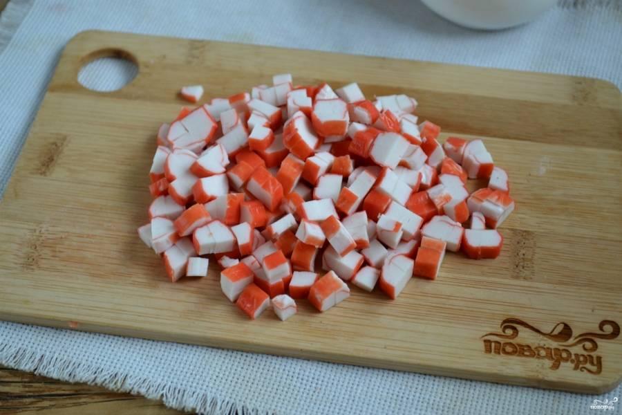 Крабовые палочки порубите на мелкие кубики.