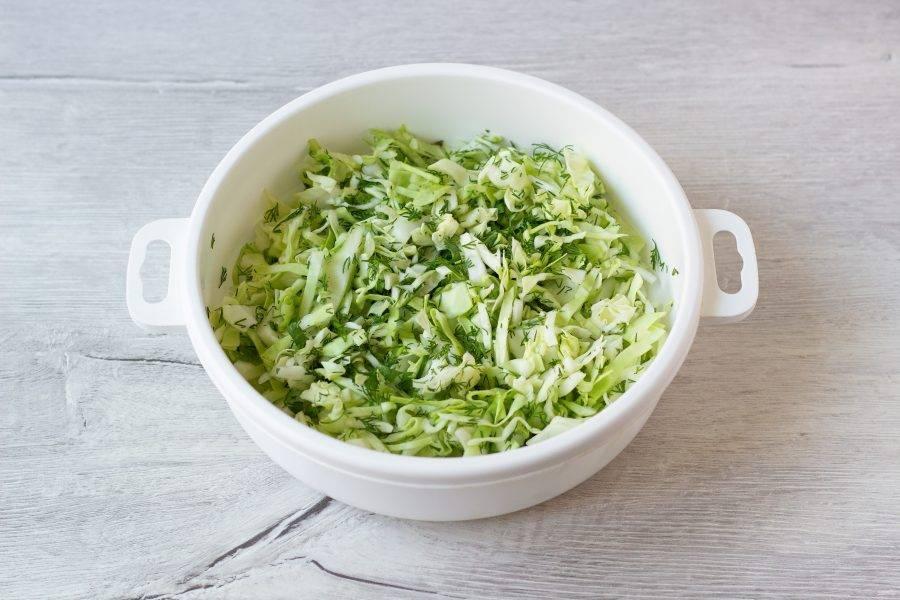 Добавьте немного соли и помните капусту с зеленью, чтобы капуста пустила сок.