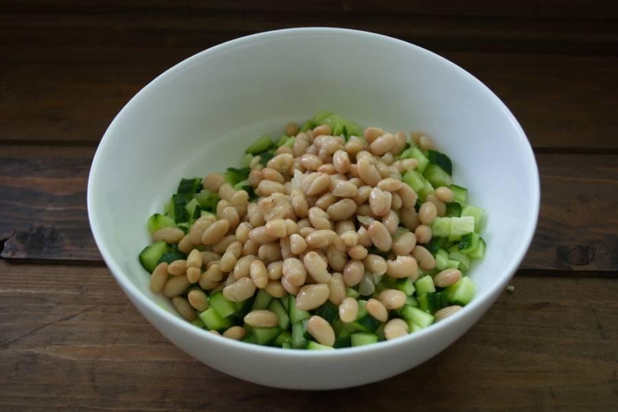 Консервированную фасоль в банке открыть. Промыть от соуса. Дать стечь воде и саму фасоль добавить в салатник к огурцам.