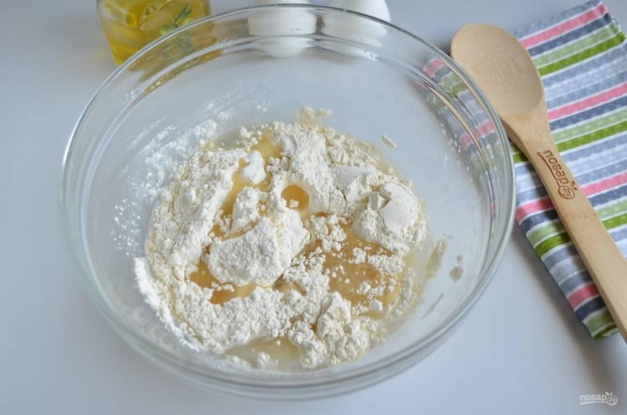 Влейте растительное масло, всыпьте муку и замесите мягкое и пластичное тесто.