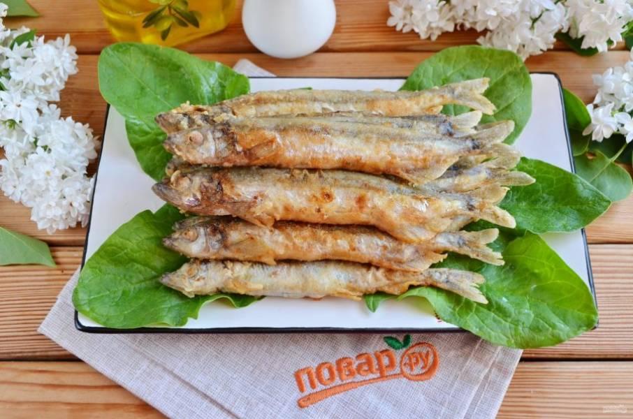 Жареная мойва на сковороде готова! Подавайте рыбку с овощами и зеленью. Приятного!