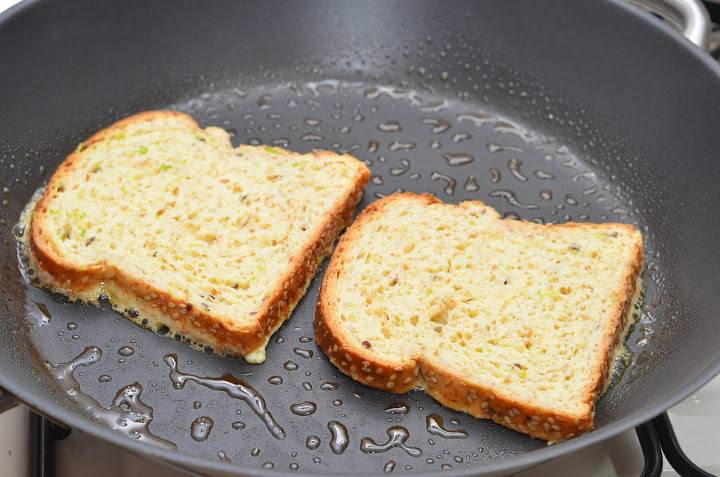 Сковородку разогреваем, смазываем ее сливочным маслом или вливаем оливковое масло и кладем ломтики. Обжариваем их на среднем огне до румяности.