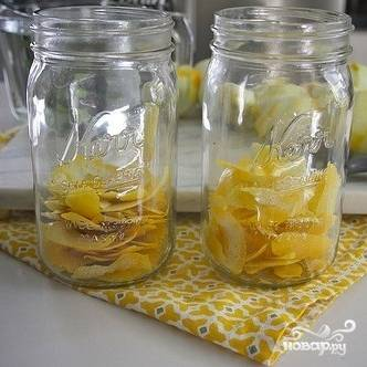 Выкладываем лимонные корки в банки.