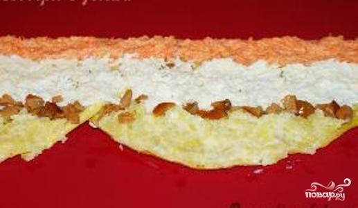 Приготовьте начинку салата. Для этого смешайте натертый на крупной терке вареный картофель с майонезом, натертый на средней терке сыр с майонезом, натертые на средней терке яйца с майонезом, натертую на средней терке морковь с майонезом, и мелко нарезанные опята с майонезом. Оставьте 10-15 красивых грибочков для украшения. Затем поочередно разложите начинки по грибам. Всего должно получится 5 равномерных слоев по всей длине блинной цепи.