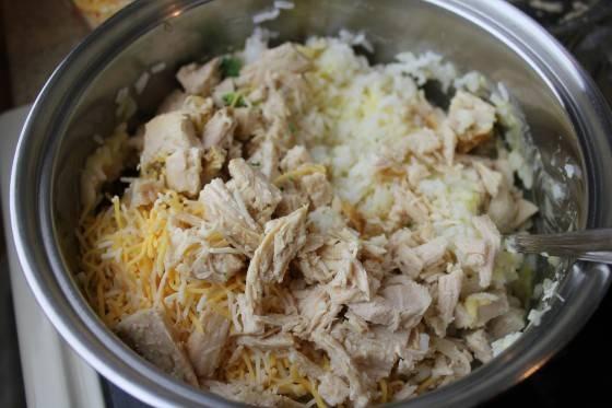4. Затем все ингредиенты надо смешать в большой миске, а именно: кусочки вареной курицы, брокколи, готовый рис, тертый сыр, соль и перец. Заливаем все сливками и еще раз перемешиваем. Кстати, часть тертого сыра оставьте, мы им добавим на блюдо перед запеканием.