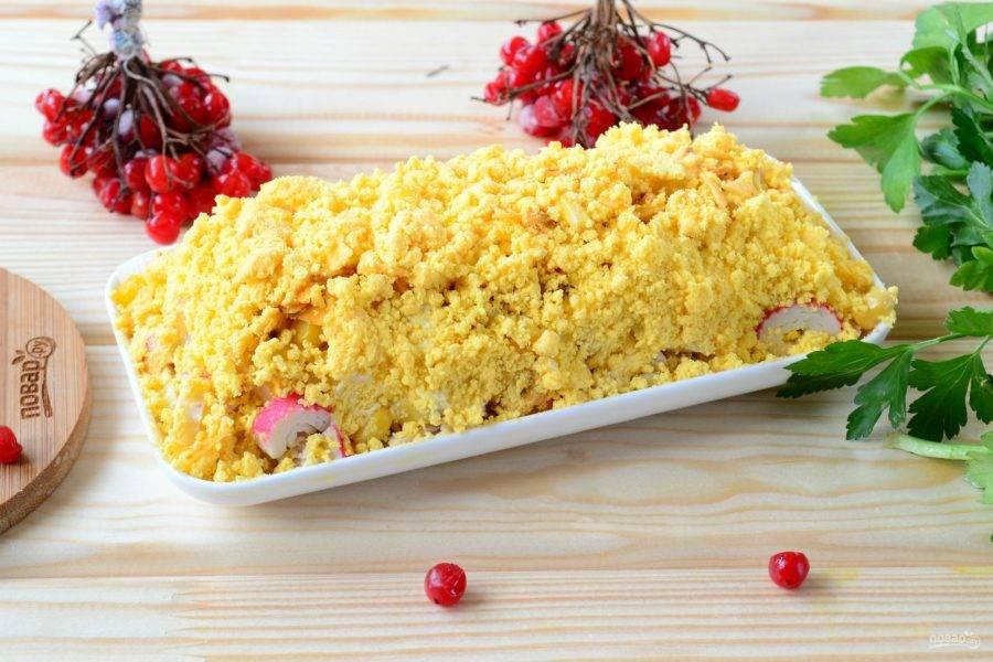 Яйца разделите на белки и желтки. Желтки сложите в глубокую мисочку и измельчите вилкой. Обсыпьте желтками нашу горку из салата. Если желток обсыпается, то еще немного смажьте майонезом.
