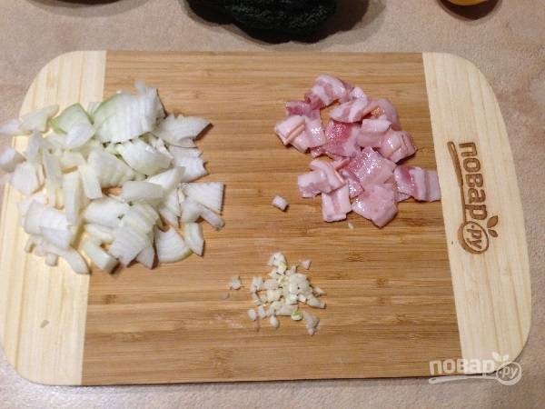 3. Бекон нарезаем на кусочки, очистим лук и чеснок. Лук нарежем четвертькольцами, а чеснок мелко порубим.
