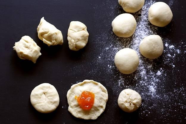 6. Затем разделить тесто на одинаковые шарики небольшого размера. Сформировать лепешку, в середину которой вложить начинку. Приготовить сладкие булочки из дрожжевого теста в домашних условиях можно не только с джемом, но и с маком, творогом, фруктами или ягодами, например.
