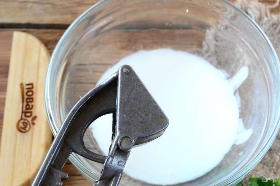 Для начала подготовьте соус. Для этого смешайте йогурт с измельченным чесноком, который можно пропустить через пресс или просто раздавить ножом, а затем мелко порубить.