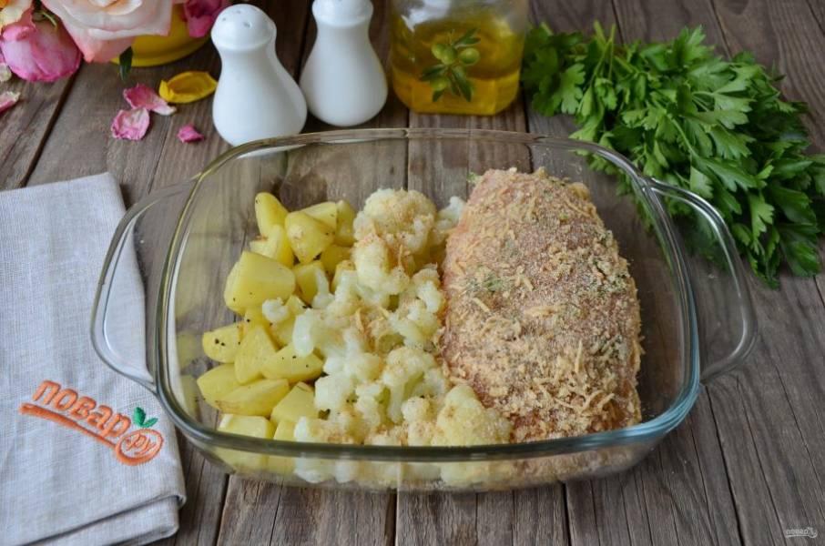 Лопаткой сдвиньте полуготовый картофель, рядом поместите цветную капусту и куриное филе. Цветную капусту можно полить растительным маслом и посыпать остатками панировочных сухарей с сыром. Поместите форму в духовку на 15 минут. Температура — 200 градусов, верхний гриль включен.