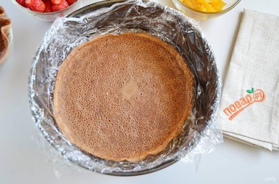 5. Разъемную форму застелите хорошо пищевой пленкой, чтобы борта тоже были прикрыты. Положите на дно первый блин, смажьте его кремом.