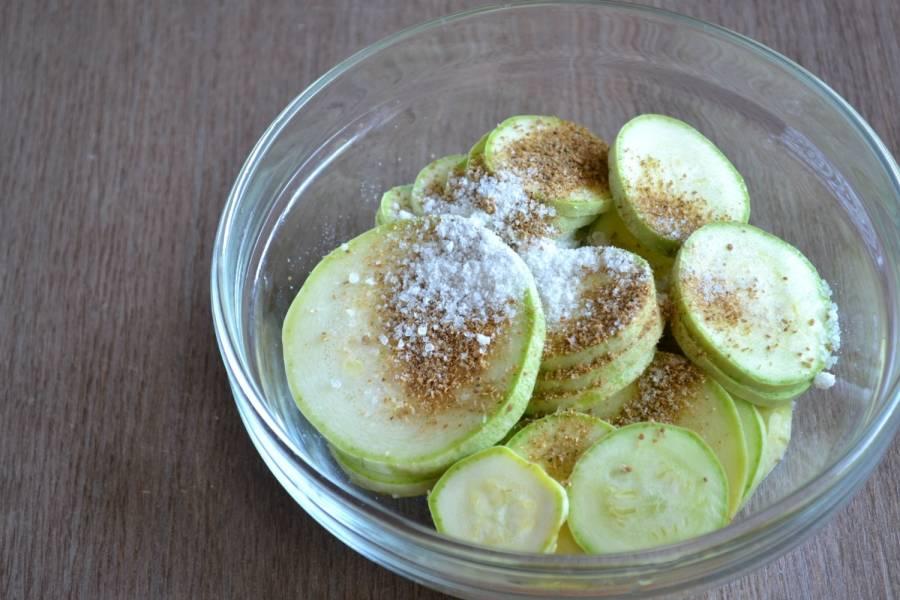 Присыпьте кружочки кабачка приправой и солью, перемешайте и оставьте на 30 минут, чтобы они пустили сок и слегка отмякли.