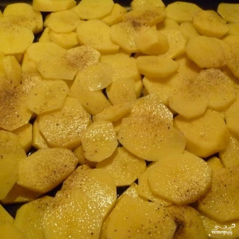 Картофель чистим, режем на тонкие пластины и укладываем на противень, смазанный маслом.
