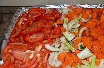 Застелите противень для запекания фольгой. Тыкву промойте, очистите от шкурки, семян и нарежьте небольшими кусочкам. Лук и болгарский перец моем и мелко нарезаем. Сельдерей и помидоры нарезаем произвольно. Чеснок очищаем и мелко режем. Все овощи кладем на противень. Посолить, поперчить, добавить тимьян и сбрызнуть оливковым маслом.