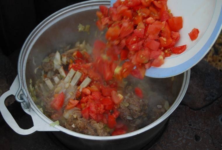 4. После капусты - измельченные помидоры. Сразу же заливаем шулюм водой, чтобы покрыла овощи и мясо. Тушим, пока капуста не станет мягкой.