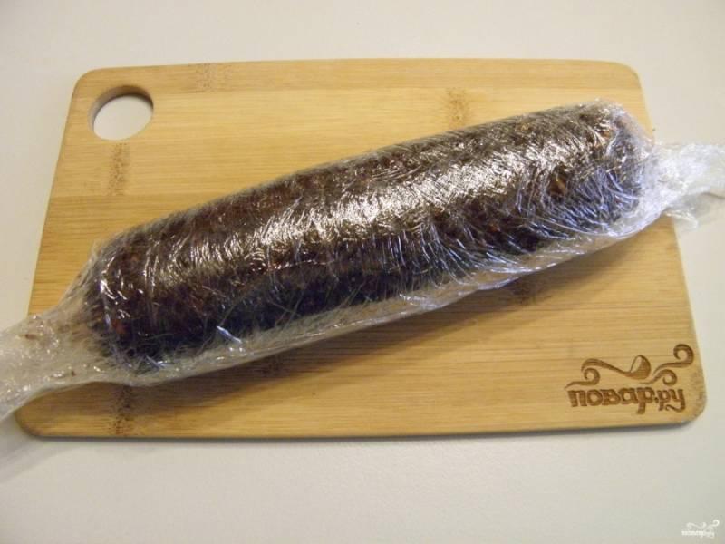 На столе разложите в несколько слоев пищевую пленку, выложите на неё половину сладкой массы, аккуратно, прижимая заверните. Края скрутите, как у конфетки, это позволит уплотнить колбаску. Уберите ее на 3-4 часа в холодильник, чтобы масло застыло и колбаска приняла форму.