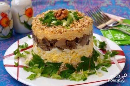 Снимаем кольцо, посыпаем салат измельченными орехами. Даем ему настояться примерно час. Перед подачей к столу дополнительно можно украсить зеленью.
