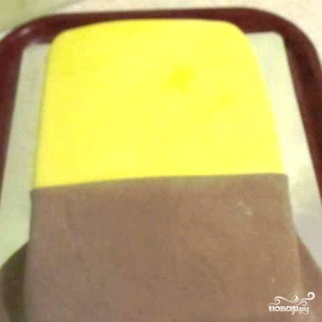 Собственно, сам торт готов, и осталось самое интересное - украсить его. Берем желтую мастику, раскатываем, покрываем ей половину нашего торта. Другую половину покрываем раскатанной коричневой мастикой. Чтобы стык двух мастик получился ровным, нужно предварительно обрезать мастику ножом со стороны, где будет стык.