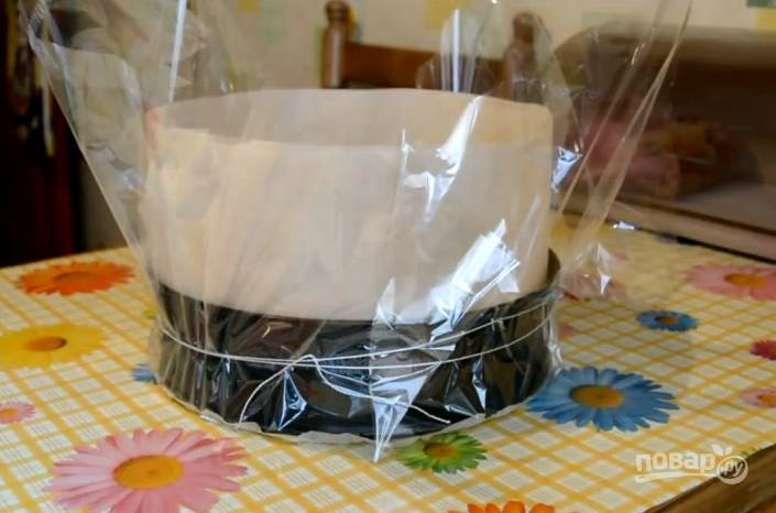 7.Выпекают чизкейк на водяной бане. Поэтому форму для выпечки обмотайте пленкой от рукава для запекания, чтобы в торт не попадала вода, и поместите в емкость с водой, чтобы она достала до половины высоты чизкейка. Поместите всё в духовку и пеките 1 час и 40-50 минут при температуре 160 градусов.