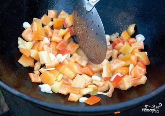 В казане разогреваем небольшое количество масла, бросаем туда перец и чеснок. Обжариваем около 2 минут на быстром огне, после чего перекладываем из казана на какую-нибудь тарелочку.