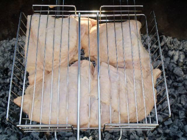 6. Когда мангал будет готов, все дрова или уголь перегорят, на решетку уложите куриные бедра. Застегните защелку на решетке. И жарьте.