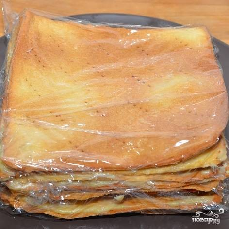 Верхний корж не промазываем. Заворачиваем торт в пищевую пленку и ставим в прохладное место (но не в холодильник) на ночь.