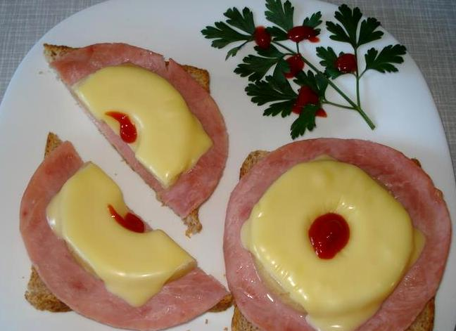 Готовые бутерброды перекладываем на тарелку, и в середину колечка ананаса добавляем немного кетчупа или вашего любимого соуса. Украшаем все свежей зеленью и подаем блюдо к столу. Приятного всем аппетита!