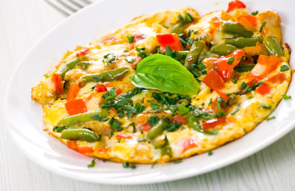 Омлет с овощами, свежей зеленью и сыром на завтрак