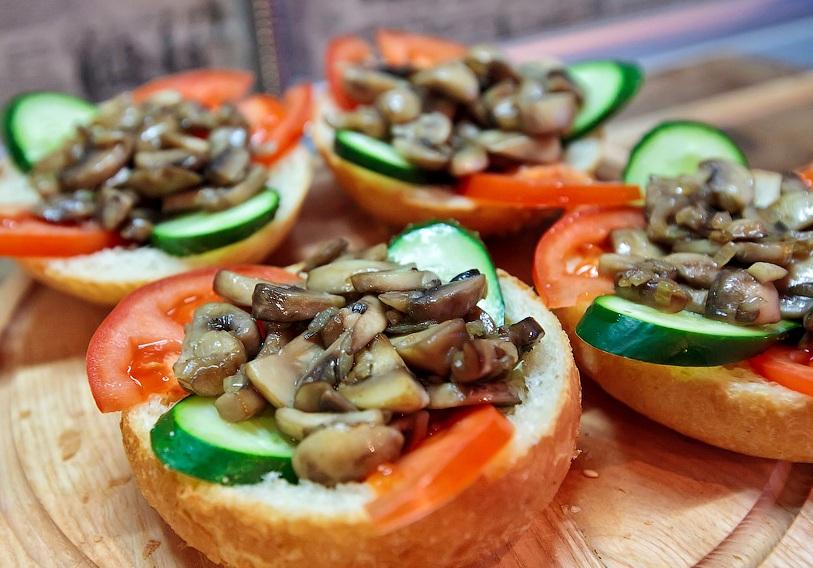 Теперь кладем в каждую выемку по несколько ломтиков помидора и огурца, сверху на овощи выкладываем обжаренные грибы с луком.