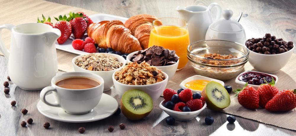 Вкусный завтрак на скорую руку: круассаны, кофе, сок, фрукты, ягоды, мюсли, овсяные хлопья