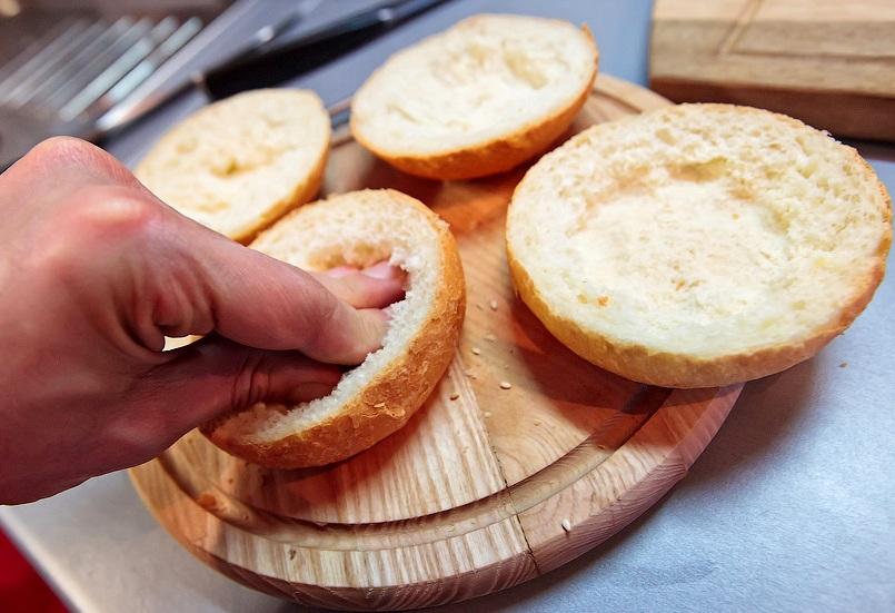 Булочки разрезаем пополам и аккуратно пальцами делаем вмятину в каждой половинке, в это углубление мы положим начинку.