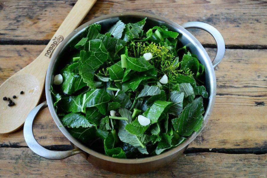 Накройте их оставшейся смесью зелени, положите чеснок и перец. Кастрюля должна получиться почти полной.