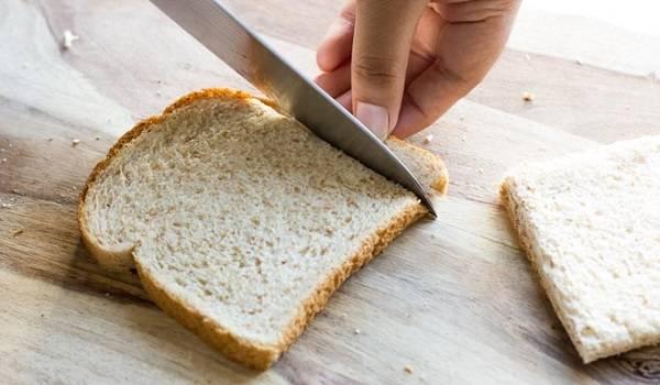 1. С ломтиков тостового хлеба (в рецепт приготовления рулетиков с колбасой и сыром лучше всего использовать именно его) аккуратно срезать острым ножом корочку.