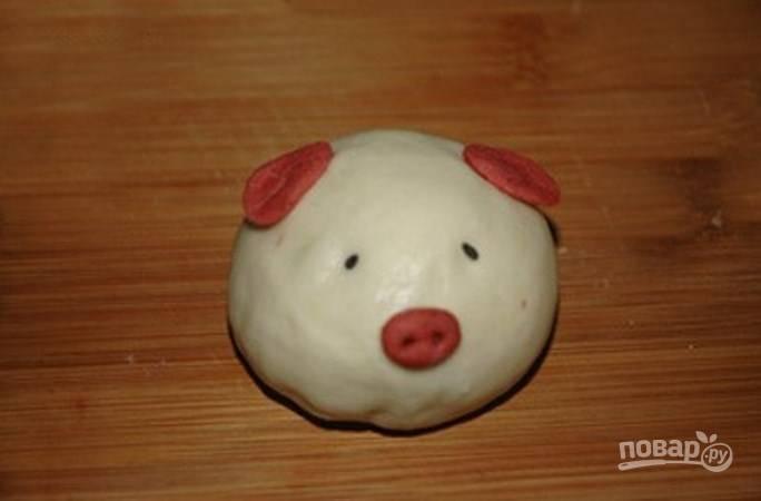 Украсьте булочку ушками, пятачком, сделанными из розового теста. Глазки сделайте из черного кунжута.