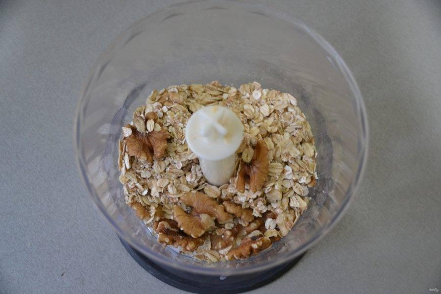 Положите в чашу блендера ядра грецких орехов и половину овсяных хлопьев.