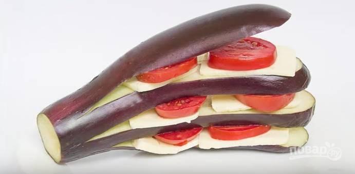 На каждый ломтик баклажана выложите сыр и кружочки помидоров.
