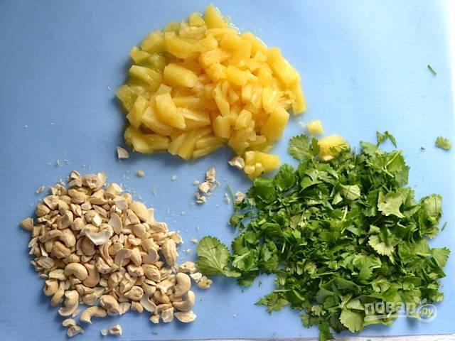 3.Ананас у меня консервированный, достаю кусочки и нарезаю их мелко, подсоленные орешки кешью нарезаю крупно, а зелень мою и измельчаю.