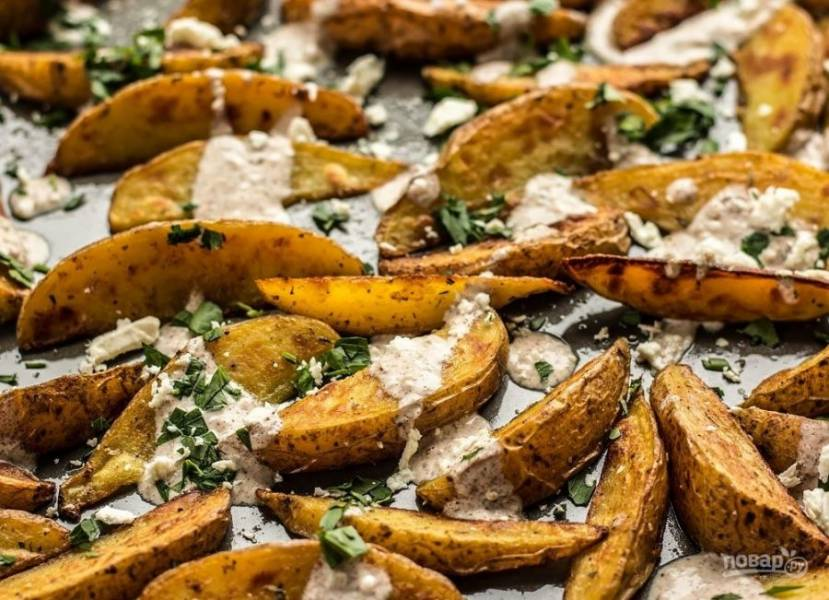 6. Петрушку помойте и измельчите, сыр «Фета» натрите. Посыпьте картофель петрушкой и сыром.