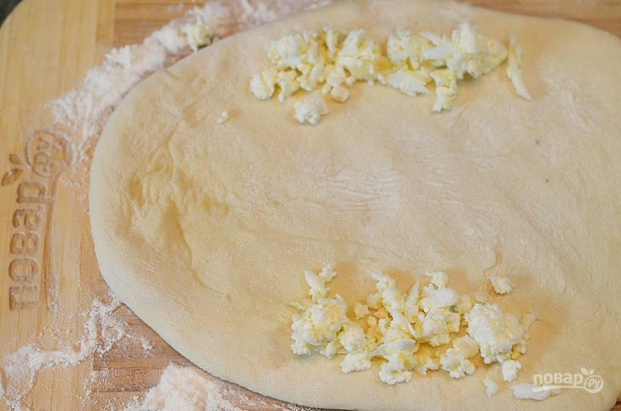4. Тесто разделите на 4 части. Каждую раскатайте в овал. По длинной стороне выложите немного отложенного сыра.