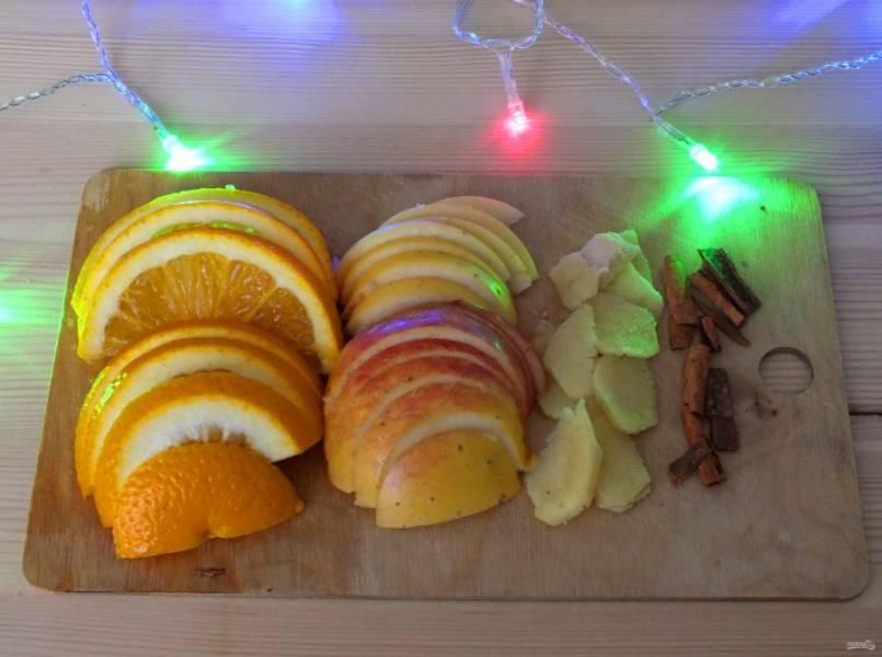 Нарежьте апельсин, яблоко полукружочками. Имбирь почистите и нарежьте пластинками (не мельчите), палочку корицы раздробите.