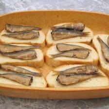 Кладем по 2 шпротины на каждый кусочек хлеба и кладем на противень.