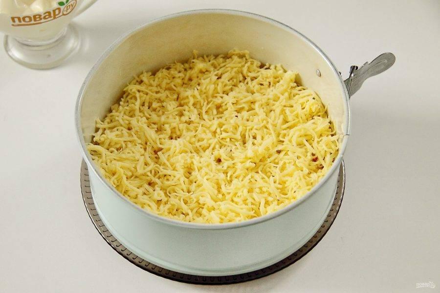 Снова смазываем слой майонезом и кладем тертый на мелкой терке сыр.