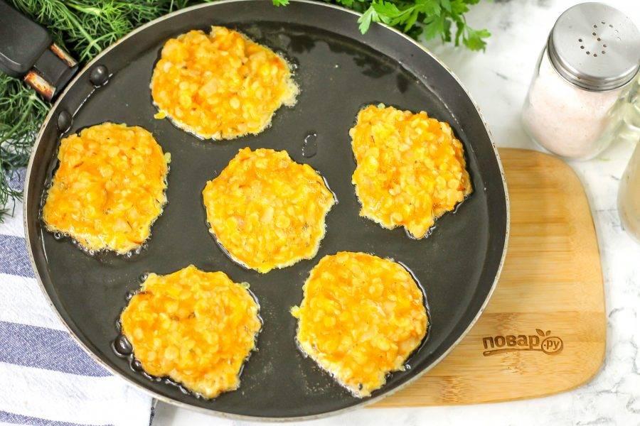 Прогрейте в сковороде оставшееся растительное масло и выложите в него чечевичную массу, слегка разравнивая ее. Обжарьте около 1-2 минут до румяности.