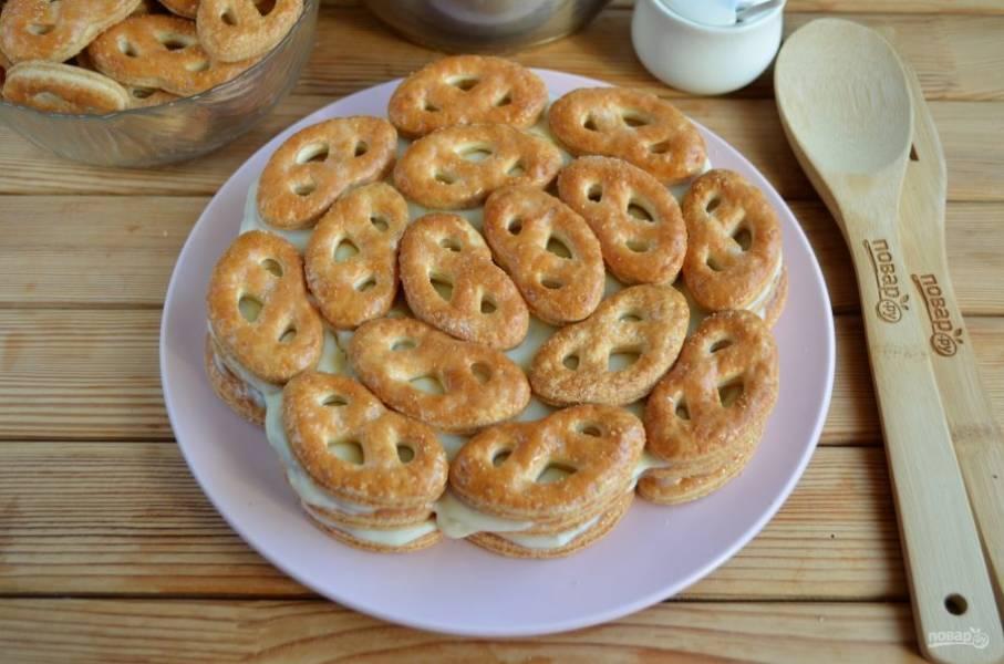 Повторяйте слои печенья и крема, пока почти не закончатся продукты. Часть печенья и крема оставьте для украшения.