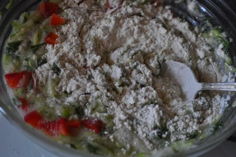 Пропустите через пресс чеснок и также добавьте в тесто вместе с мукой и специями. Перемешайте и пожарьте оладьи на хорошо разогретой сковороде с двух сторон до готовности.