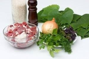 Подготовим необходимые ингредиенты: жирную мякоть свинины, репчатый лук, рис, виноградные листья, базилик, мяту, петрушку, укроп, соль и перец. Рис отварить до полуготовности в подсоленной воде, на это уйдет минут 10 после закипания воды.