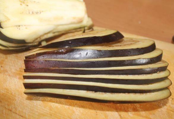 Баклажаны моем и тонким острым ножом нарезаем на тонкие пластинки. Складываем нарезанные баклажаны в глубокую миску, добавляем чайную ложку соли, доливаем воду, чтобы она покрыла баклажаны. Вымачиваем минут 20-25.