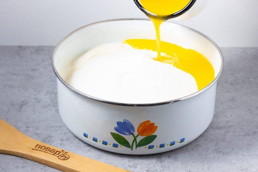 По истечении времени добавьте сахар, ванилин, разрыхлитель и растопленное сливочное масло. Тщательно всё перемешайте.