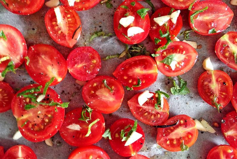 Сбрызгиваем томаты оливковым маслом, солим и перчим по вкусу. Присыпаем измельченным чесноком и зеленью. Подсушиваем в духовке 6-7 часов.